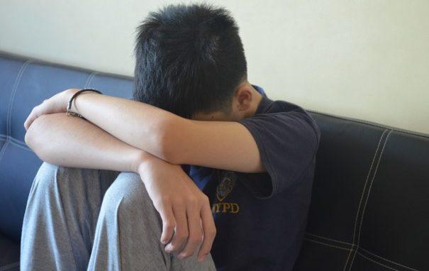 En jongen zit verdrietig in een zetel.