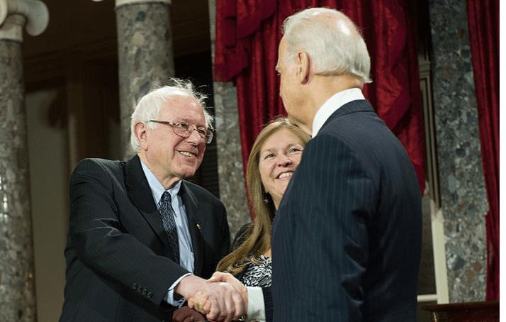 Bernie Sanders en Joe Biden schudden elkaar de hand.