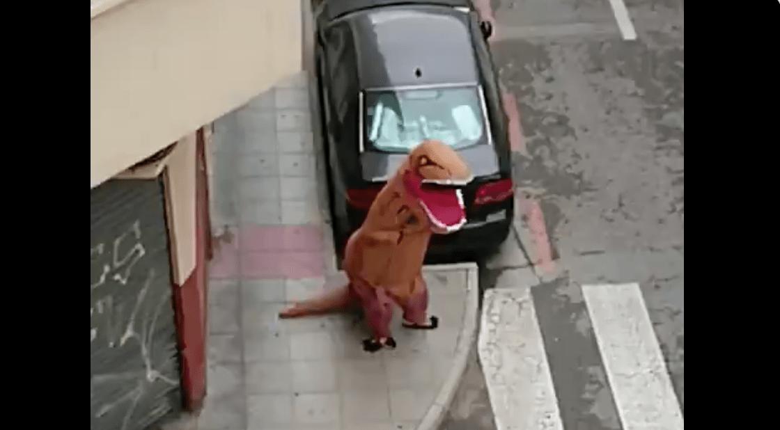 Een persoon in Madrid gaat als Tyrannosaurus rex verkleed de straat op om lockdown te ontwijken tijdens verspreiding van coronavirus.