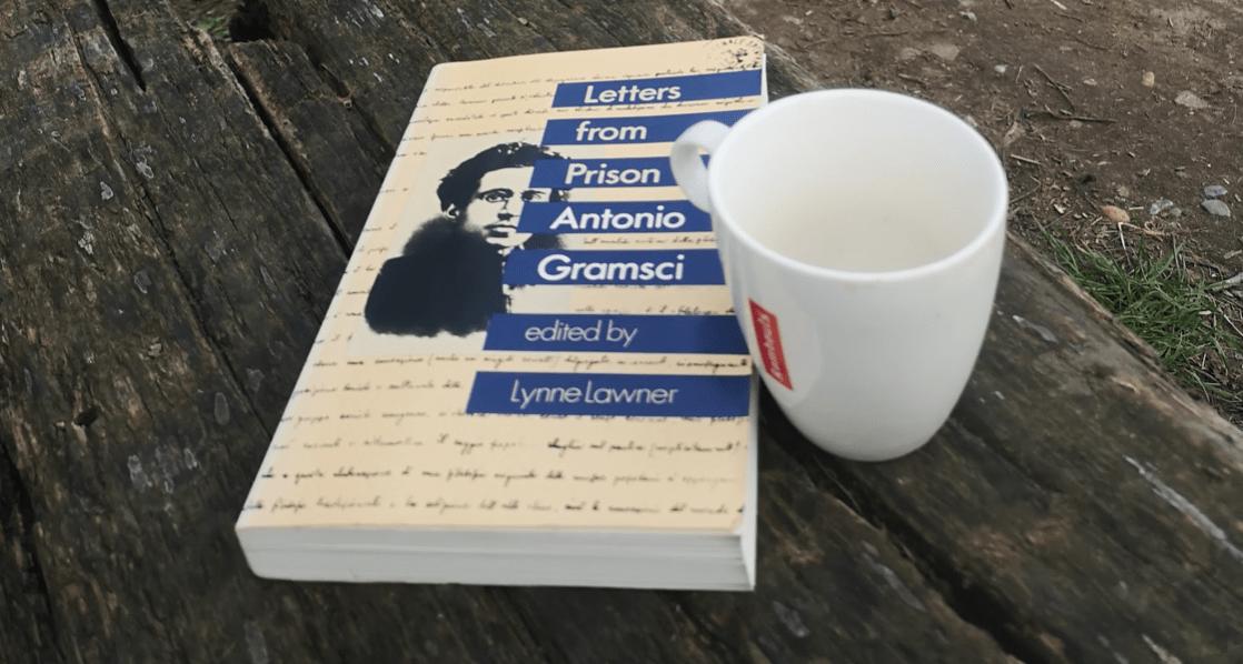 Het boek 'Letters from prison' van Antonio Gramsci op een tafel met ernaast een kop koffie, op een landbouwveld.