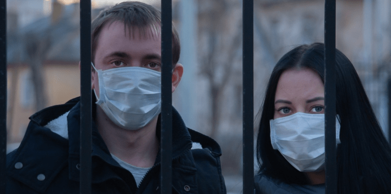 Twee mensen met mondmasker op achter tralies.