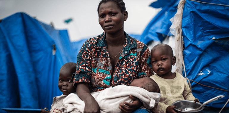 Moeder met 3 kinderen in een Afrikaans land.