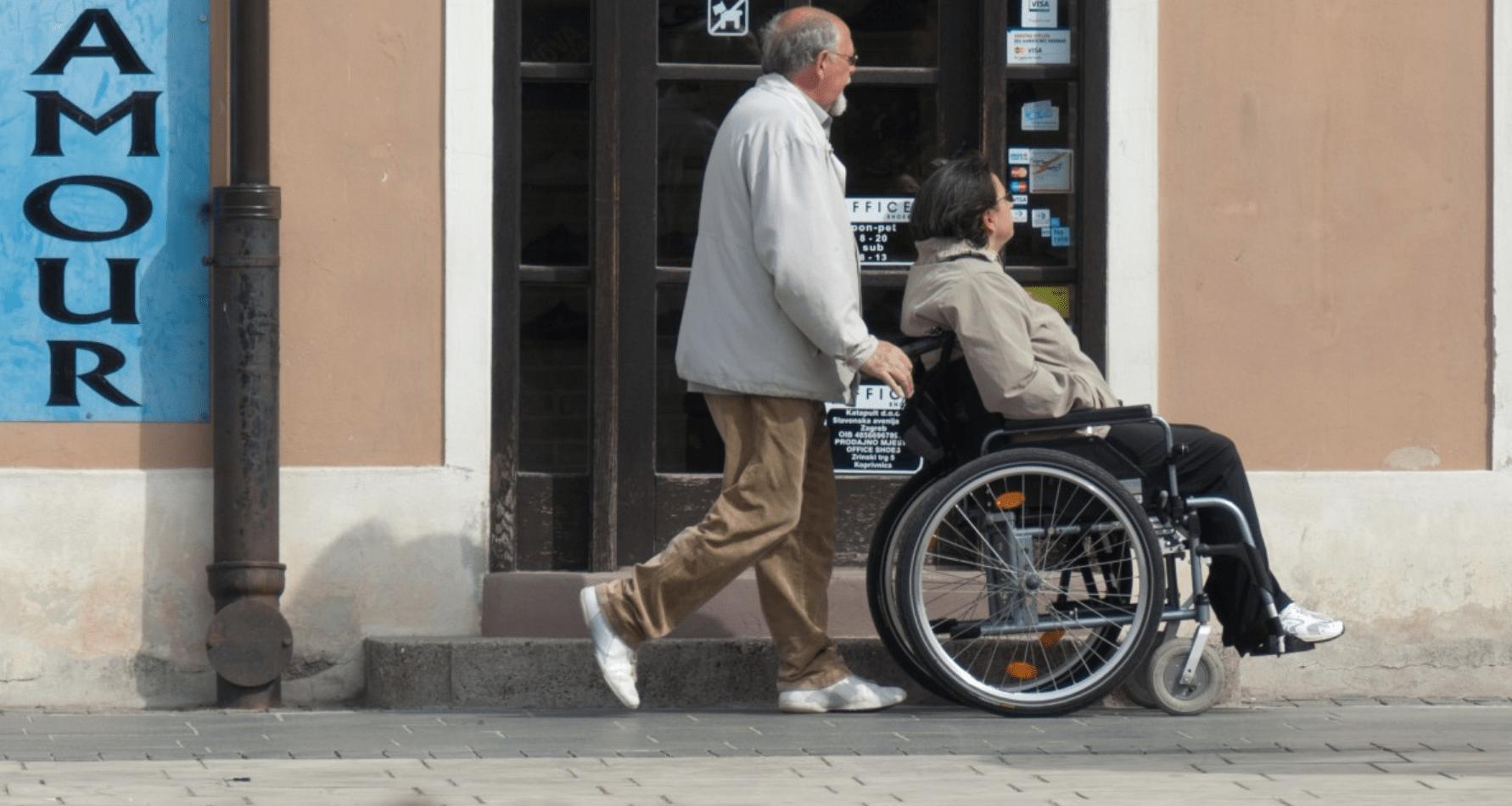 Persoon duwt een andere persoon in een rolstoel.