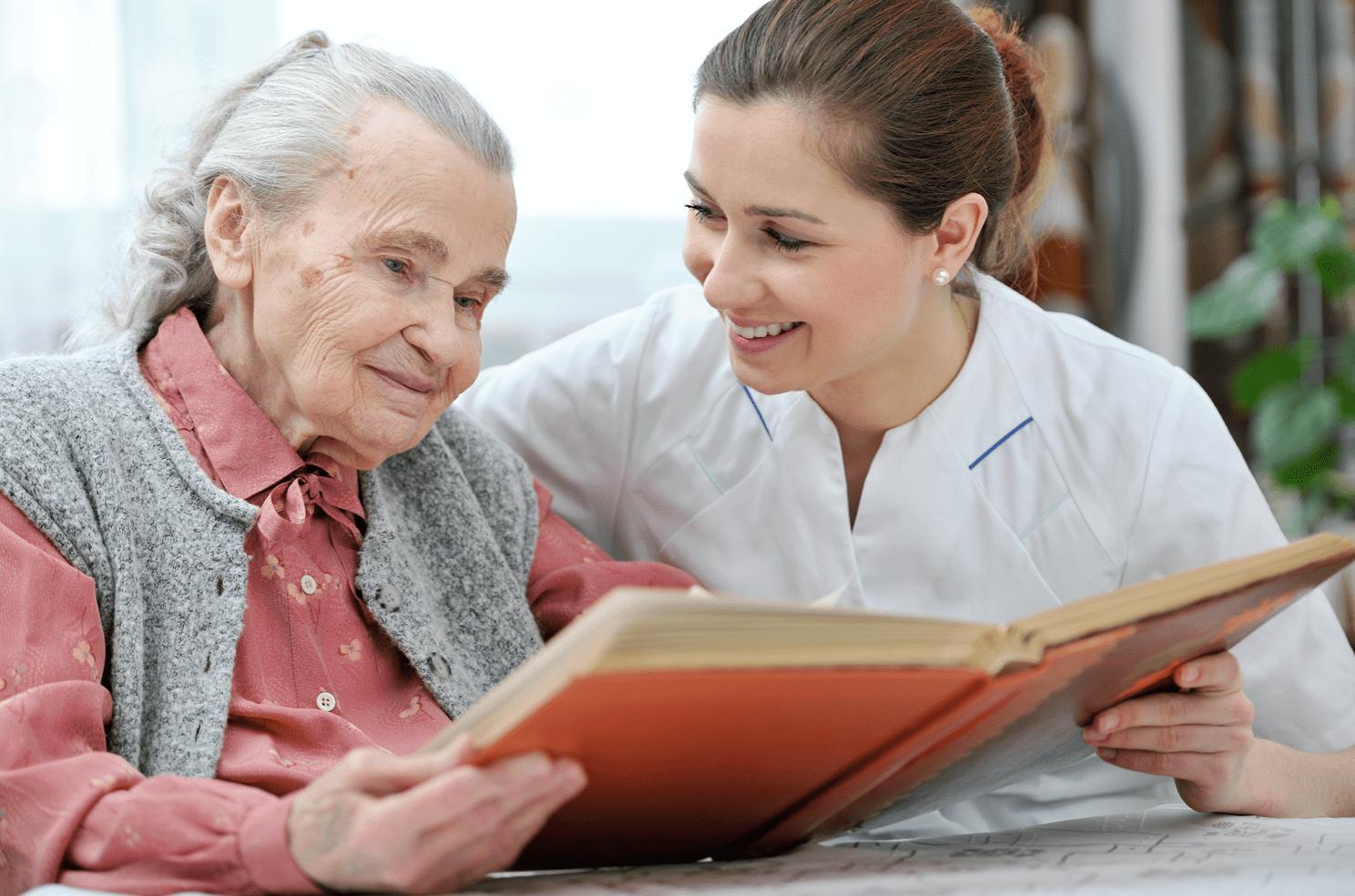 Zorgmedewerkster leest voor aan een oudere vrouw.