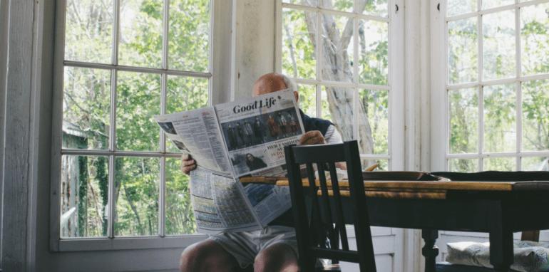 Oudere man leest de krant in zijn huis.