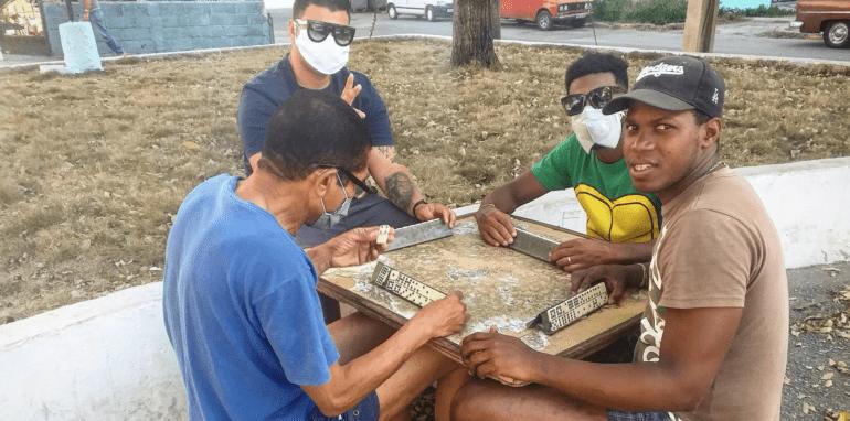 Vier vrienden op Cuba spelen buiten domino met mondmasker op.