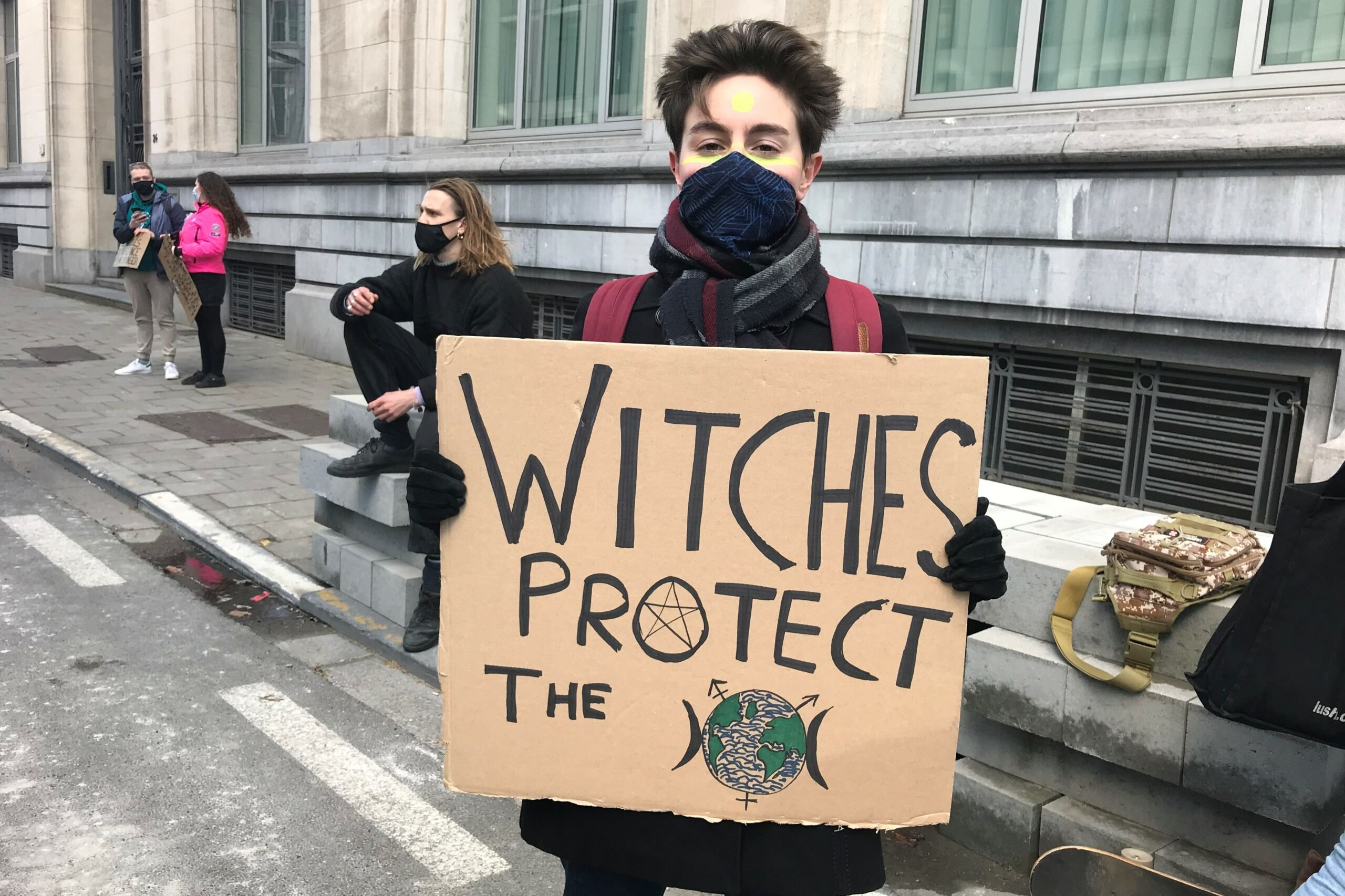 """meisje met protestbord """"witches protect the earth"""""""