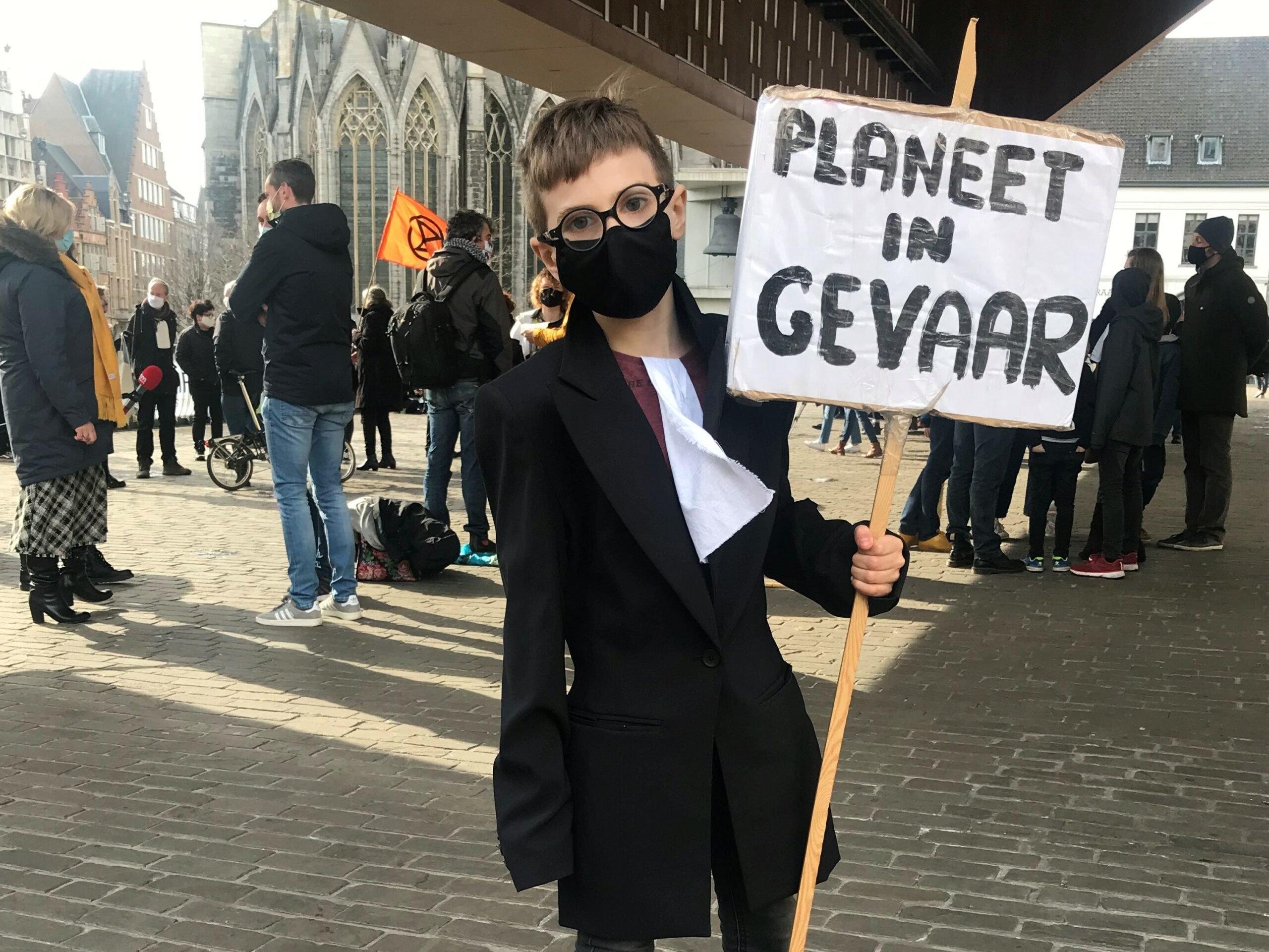 """jongen met protestbord """"planeet in gevaar"""""""