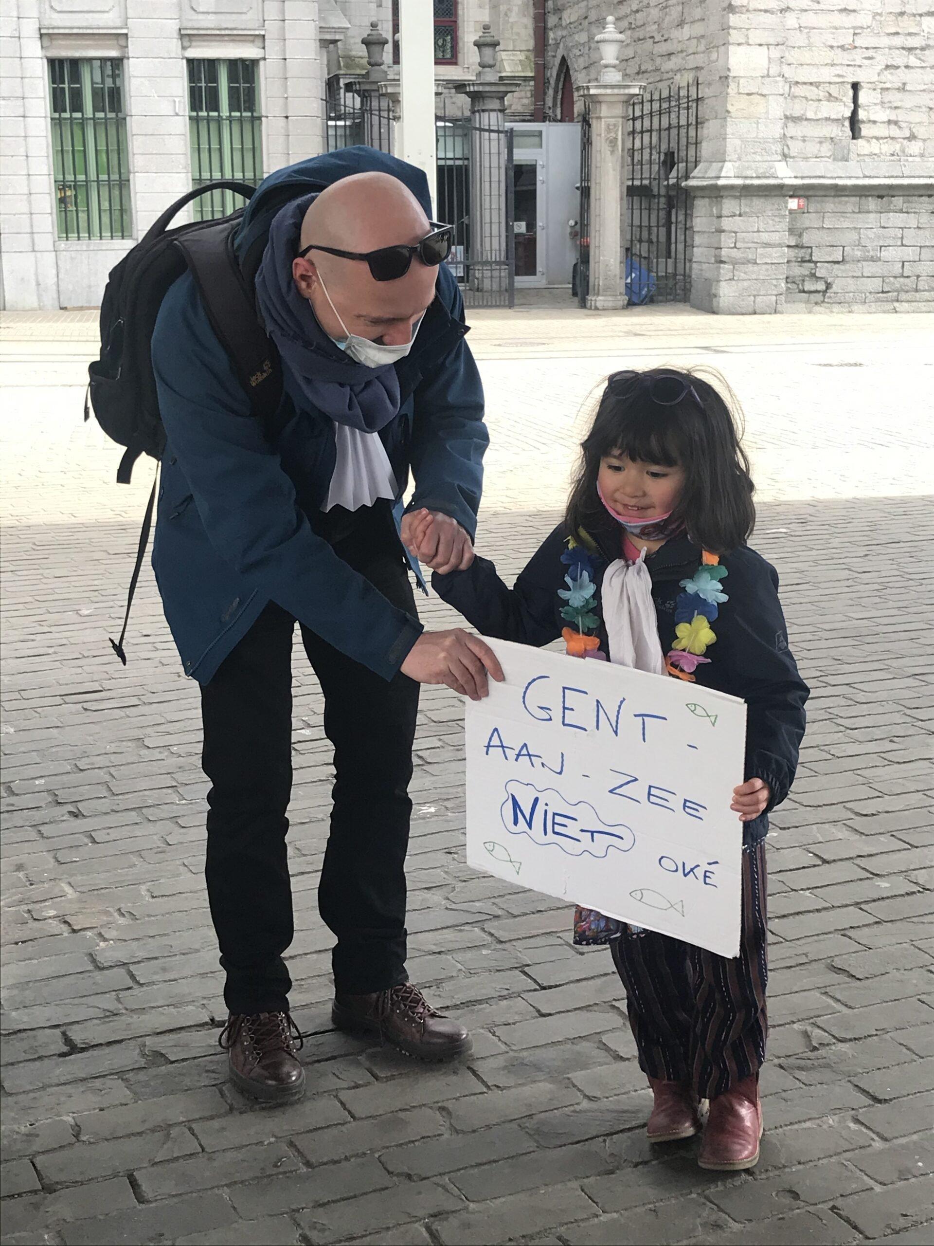 """vader met dochtertje en bord """"Gent aan zee niet oké"""""""