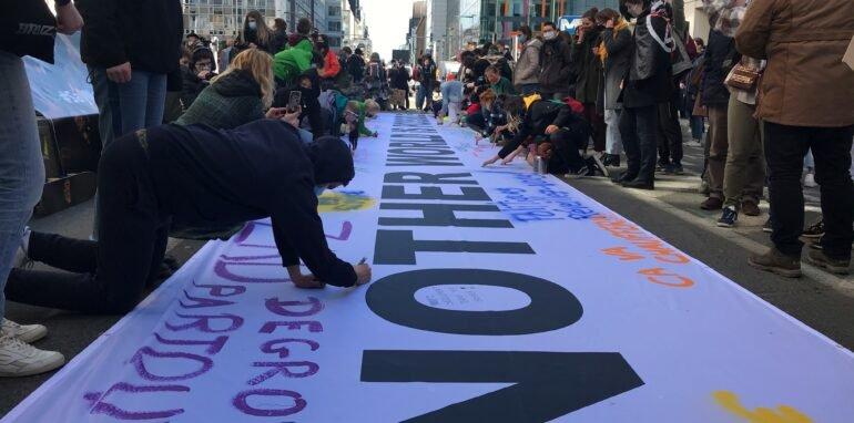 grote banner in het midden van de Wetstraat met mensen errond