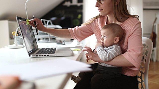 vrouw werkt met baby op schoot