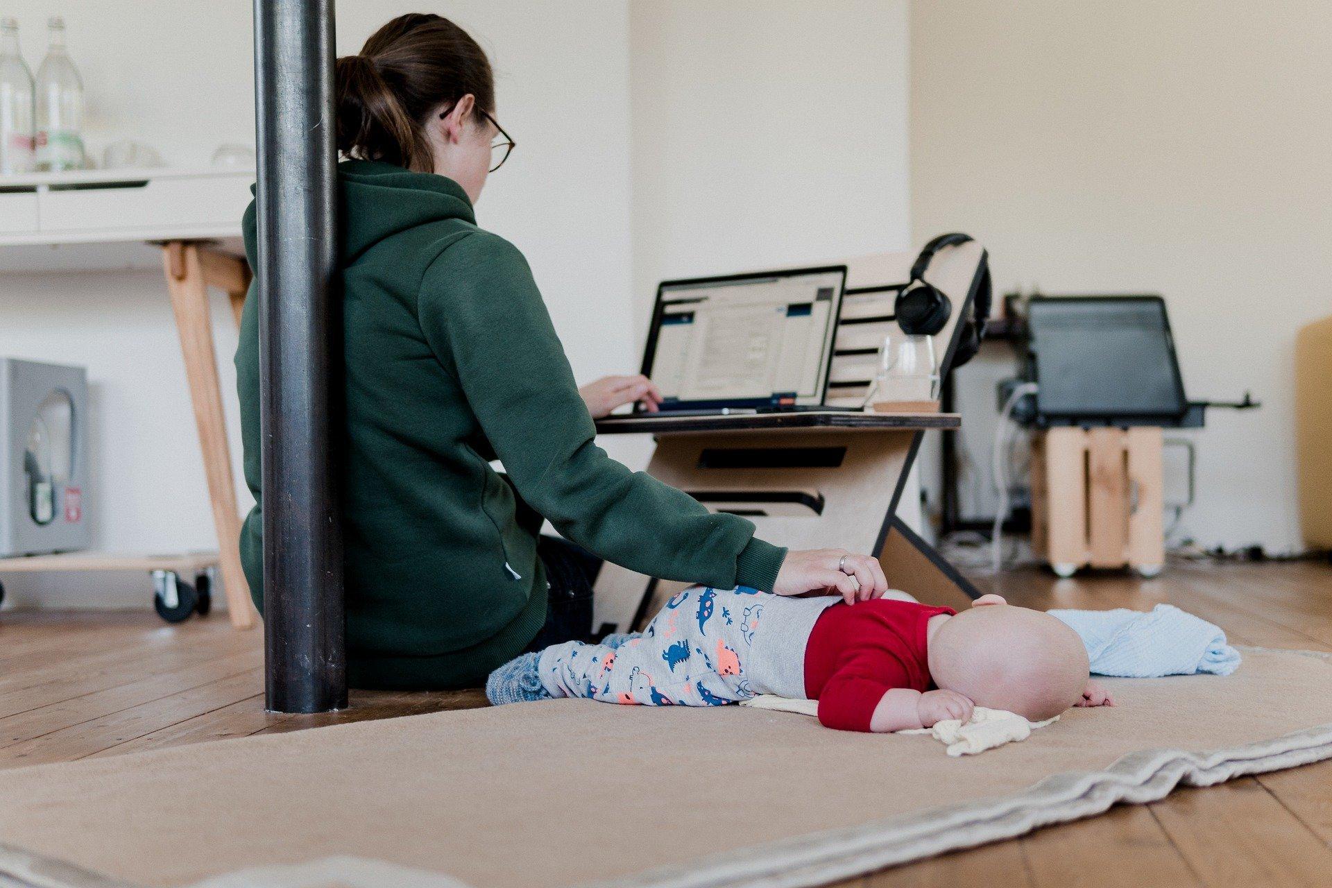 vrouw werkt op haar laptop met haar baby ernaast