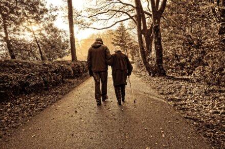 vrouw met witte stok loopt ingehaakt naast een man