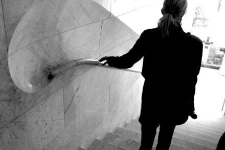een vrouw gaat de trap af en houdt de leuning vast