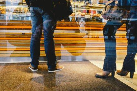 benen van een man en een vrouw voor de toonbank van een bakkerij