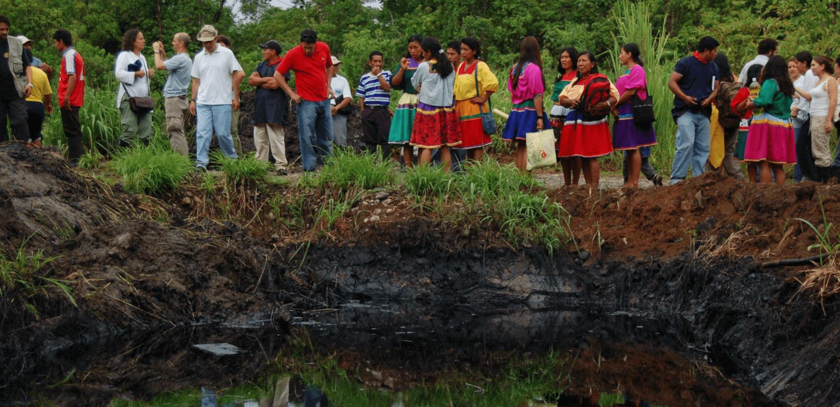 Lokale bewoners staan rond een door oliesmurrie vervuilde vijver in hun dorp in Ecuador.